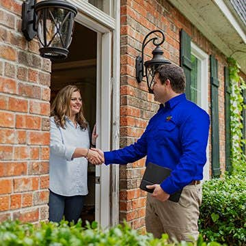 a friendly tech greeting a homeowner