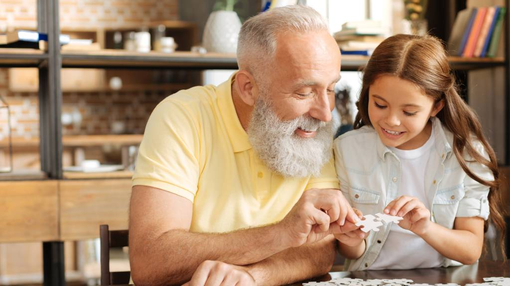 grandfather doing puzzle with young girl