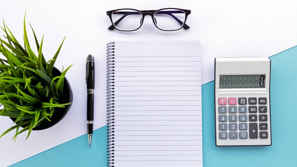 pen, paper, calculator and glasses on table to help manage a funeral insurance policy