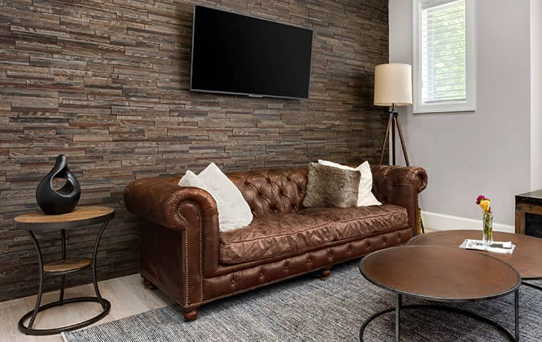 inside home office with worn leather couch lined with throw pillows