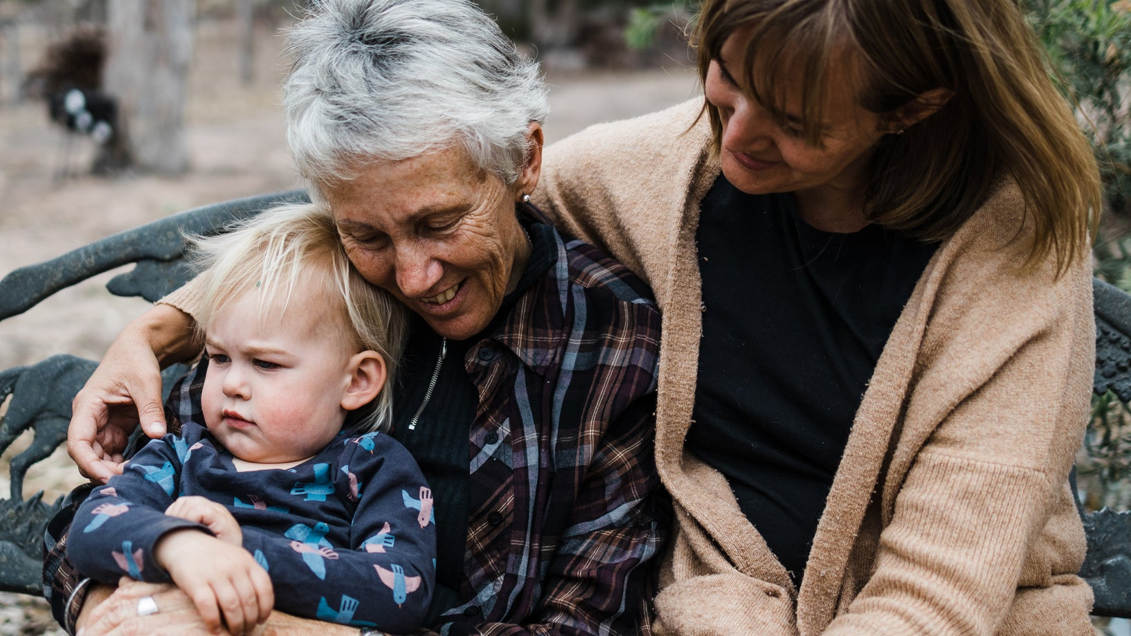 <p>toddler, grandmother and mother sit together outdoors</p>