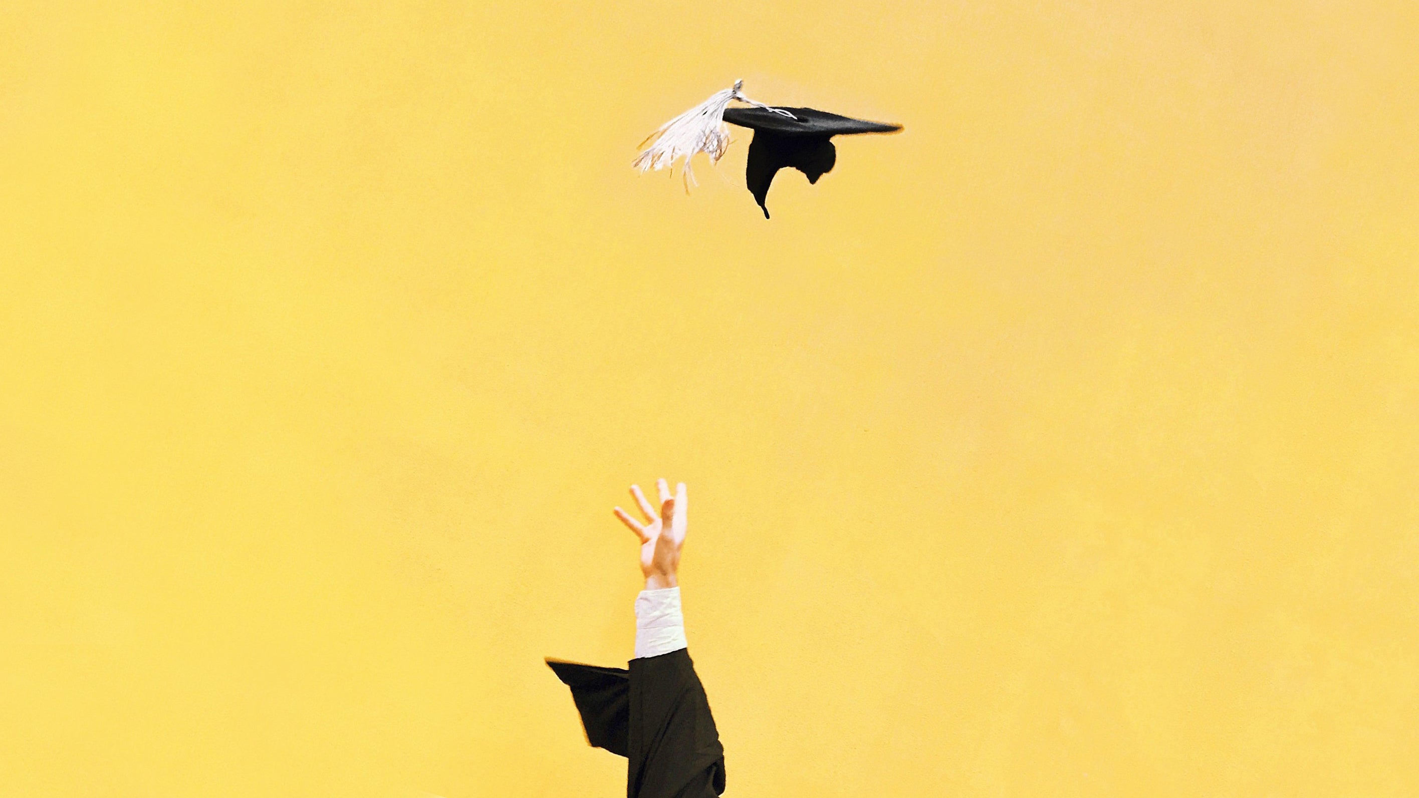 <p>Hand throwing mortarboard on yellow background.</p>