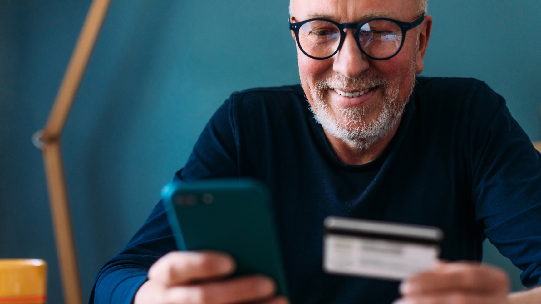 <p>Close up of a fine-looking middle aged man using his mobile phone and his credit card, shopping online</p>