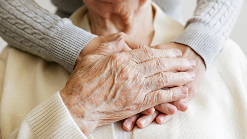 <p>Image of hands, an elderly woman's hand rests on her daughter's two hands on her chest, the daughter is standing behind her.</p>