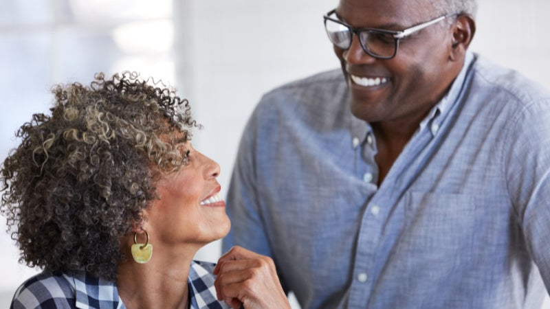 <p>Couple in their 50s or 60s smiling at each other happily as they look at finances on the computer together</p>