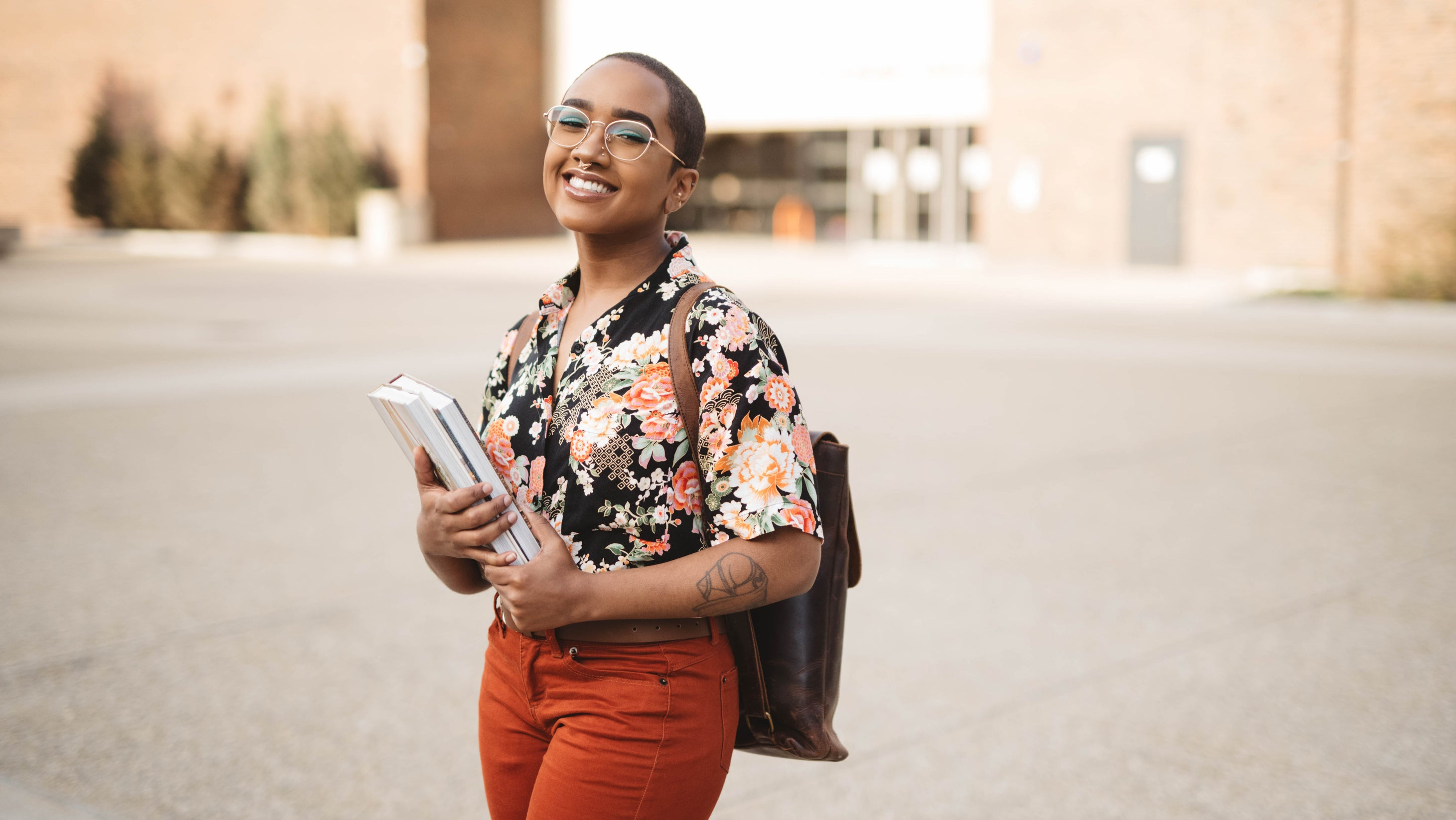 <p>A proud college student, holding her books and smiling wide, wearing a flowered shirt</p>
