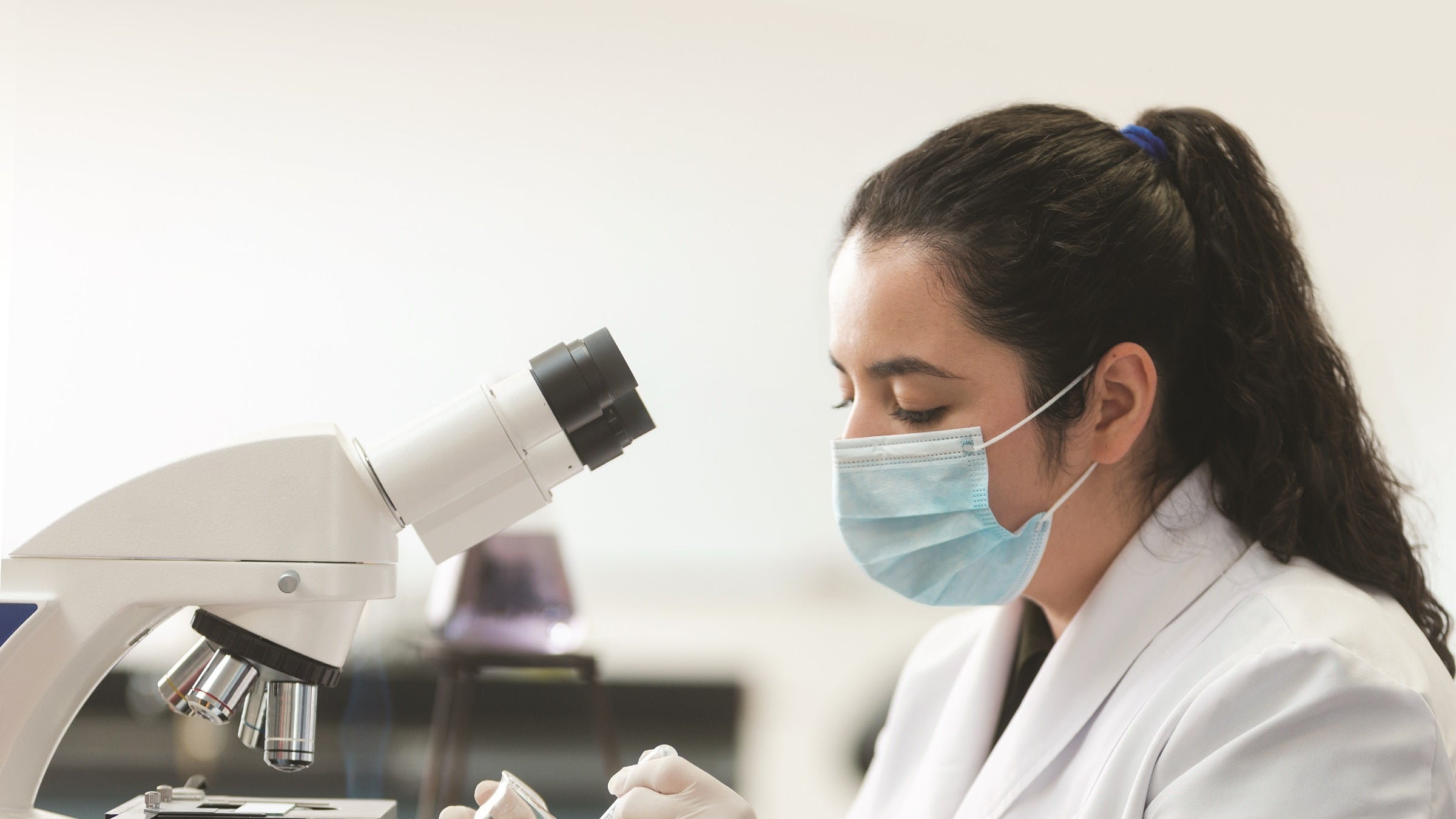 Technician looking at lab samples with a microscope