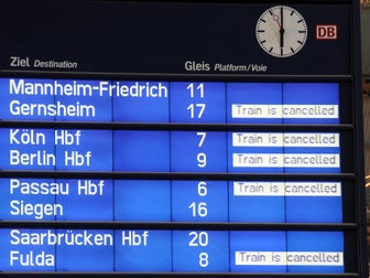 A picture of a train station board with delayed and cancelled trains.