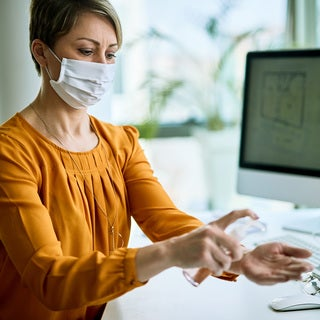 Woman in mask putting hand sanitizer on her hands at her desk