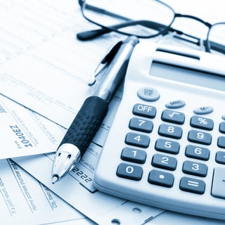 Pen next to glasses and a ten-key calculator