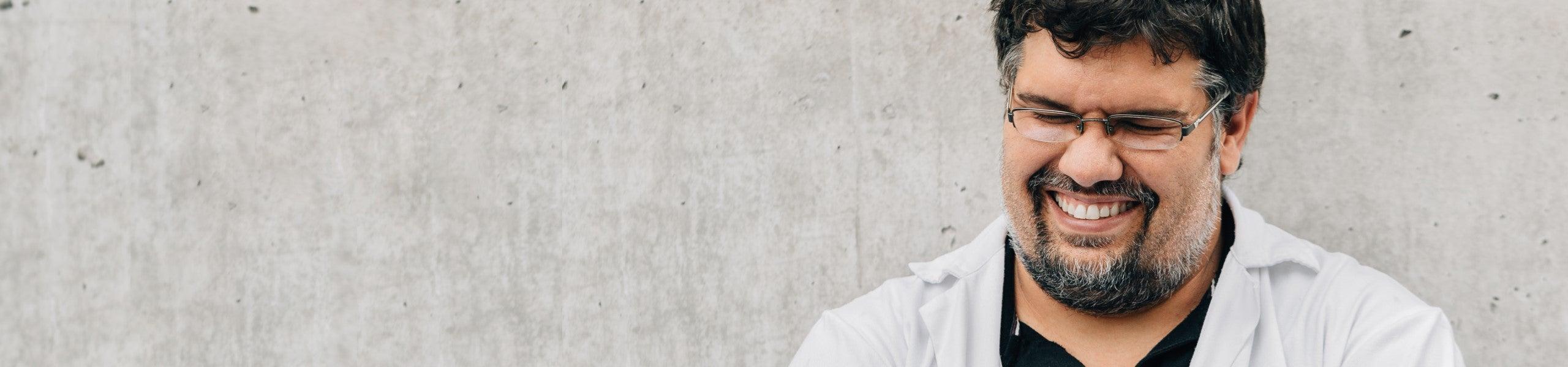 Man in white lab coat smiling