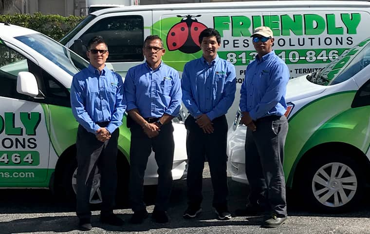 friendly pest solutions team in front of company vehicles in brandon florida