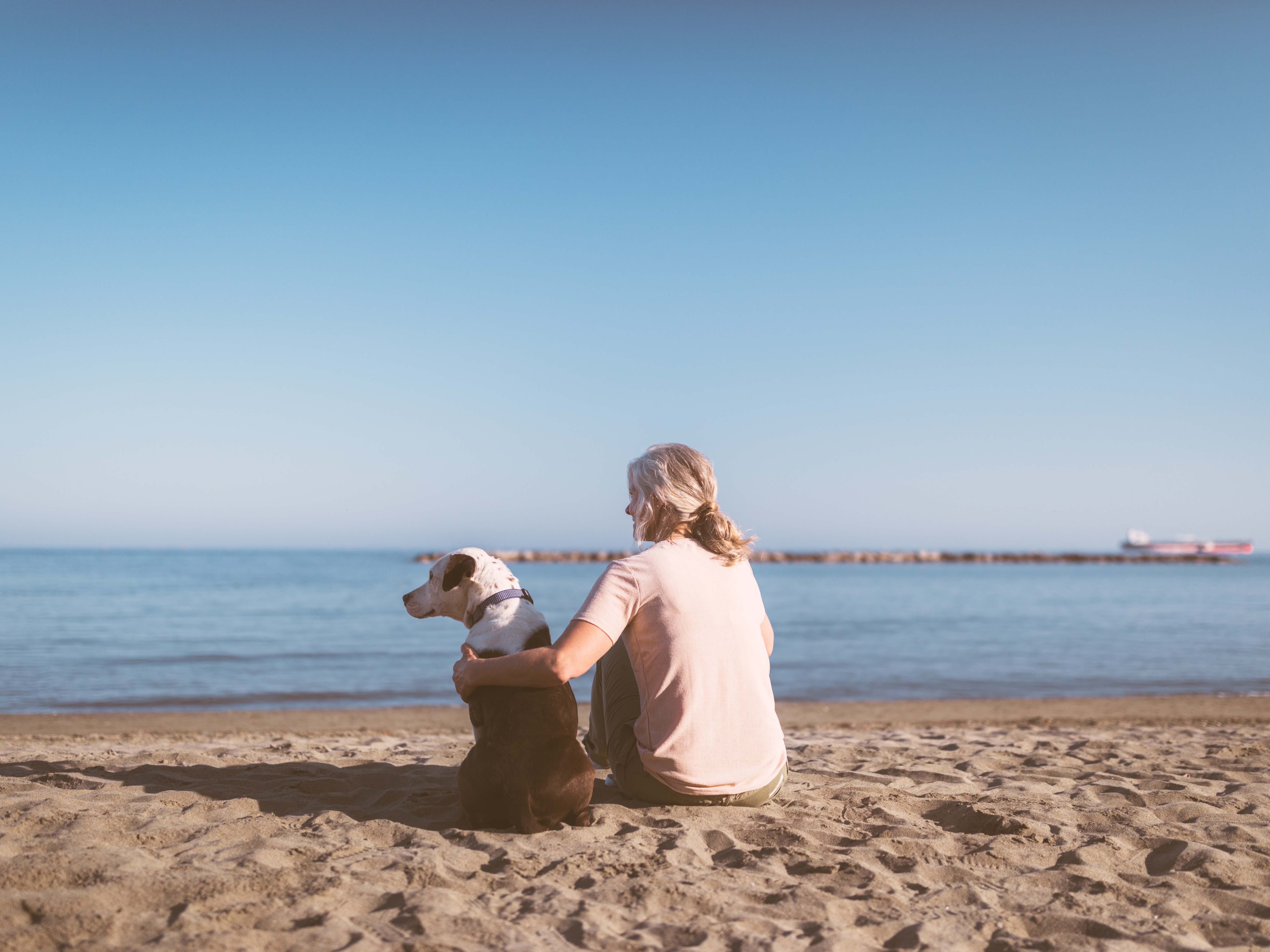 Image of woman with dog on beach
