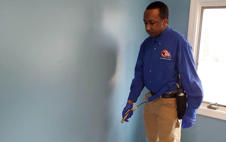 technician spraying bug spray in an office room