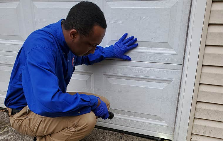 technician inspecting the outside of a garage in home
