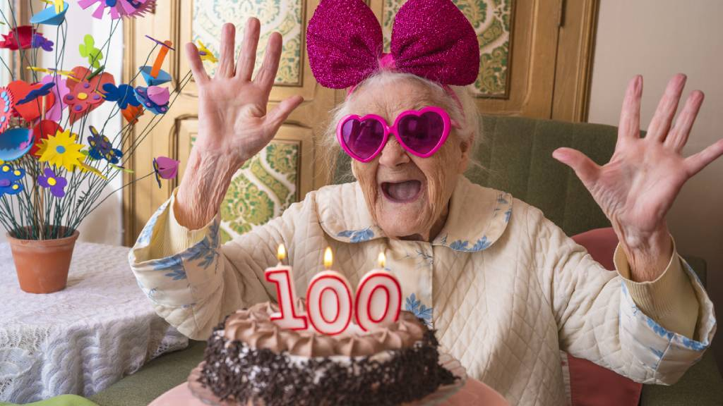 woman celebrates 100th birthday with cake and decorations
