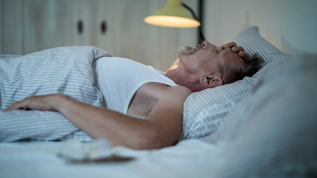 Senior man sleepless and frustrated in bed at night.