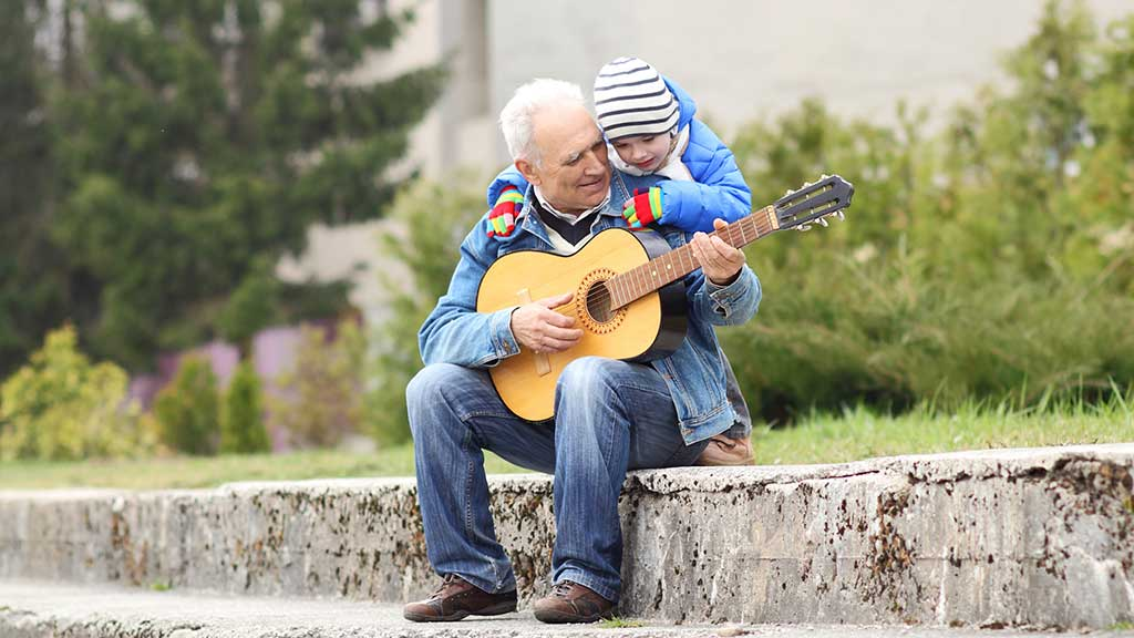 grandfather plays guitar to grandson in the park