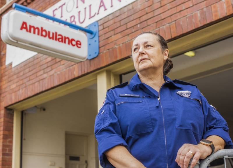 Paramedic Karen Martin stands in front of an emergency sign