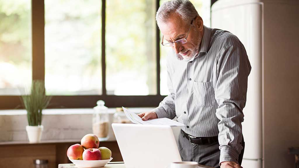 older man using laptop
