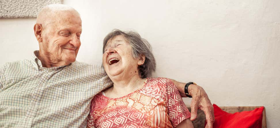 A senior couple sit on a couch, laughing and enjoying each other's company.