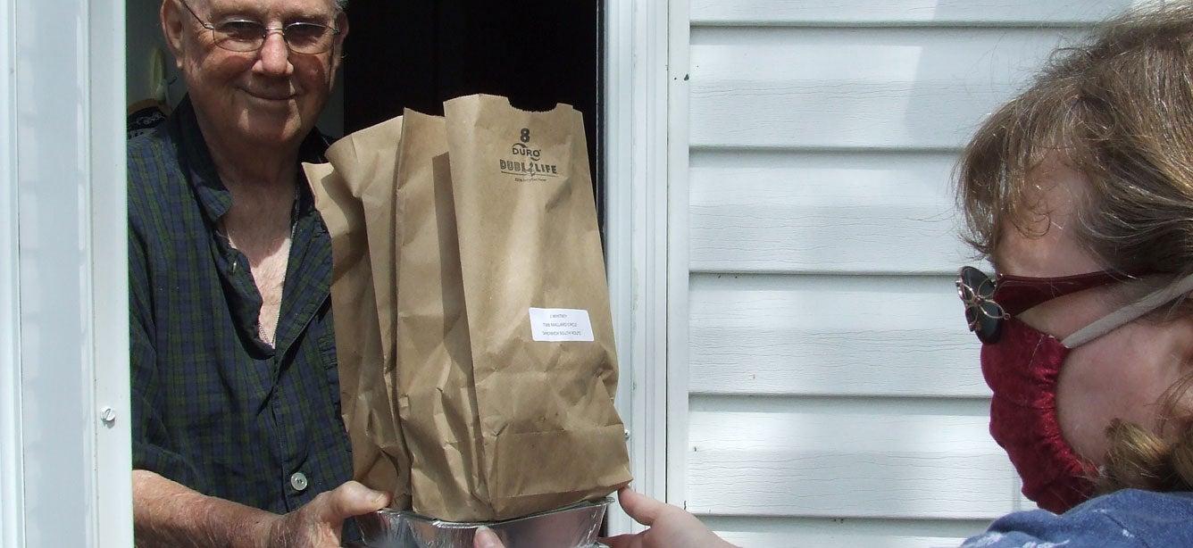 Volunteer Beverly Gorman delivering Meals on Wheels to John Whitney, June 2020.