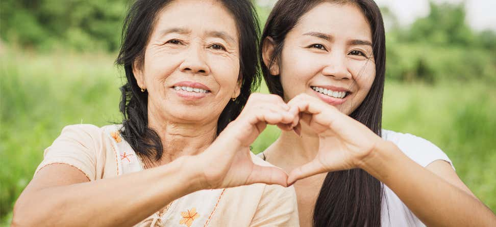 A senior Asian mom is making a heart shape with her hand and her daughter's hand.