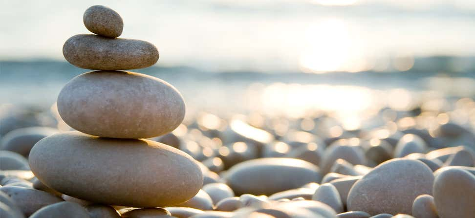 A variety of rocks are balanced vertically on the beach.