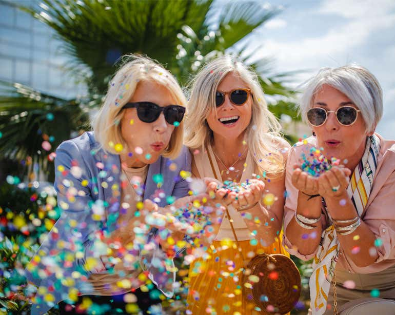 Three senior women wearing sunglasses are outside in the sun, blowing confetti while at a birthday party.