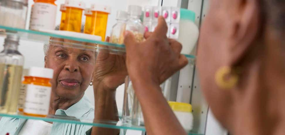 An older black women is reaching for a prescription bottle in her medicine cabinet.