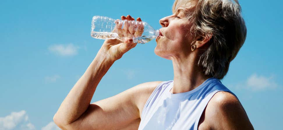 A senior Caucasian woman is drinking water from a water bottle outside.
