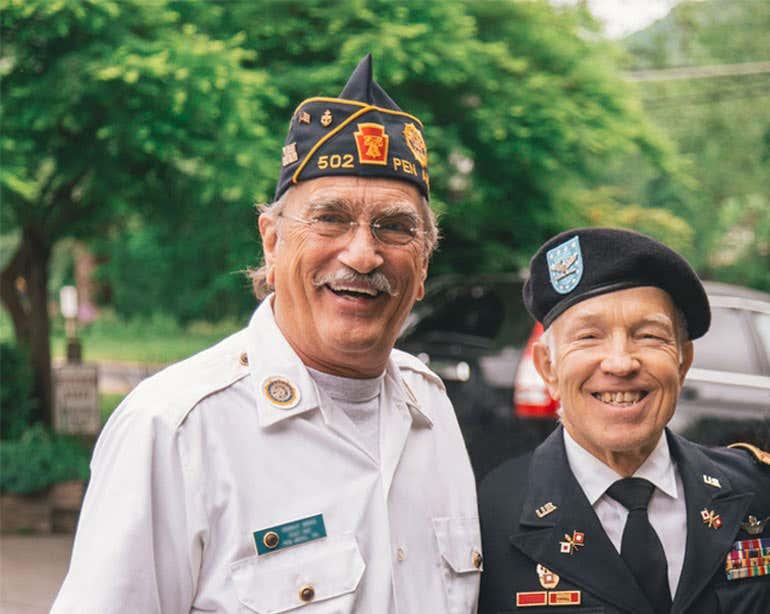 Two senior male veterans smile for the camera.