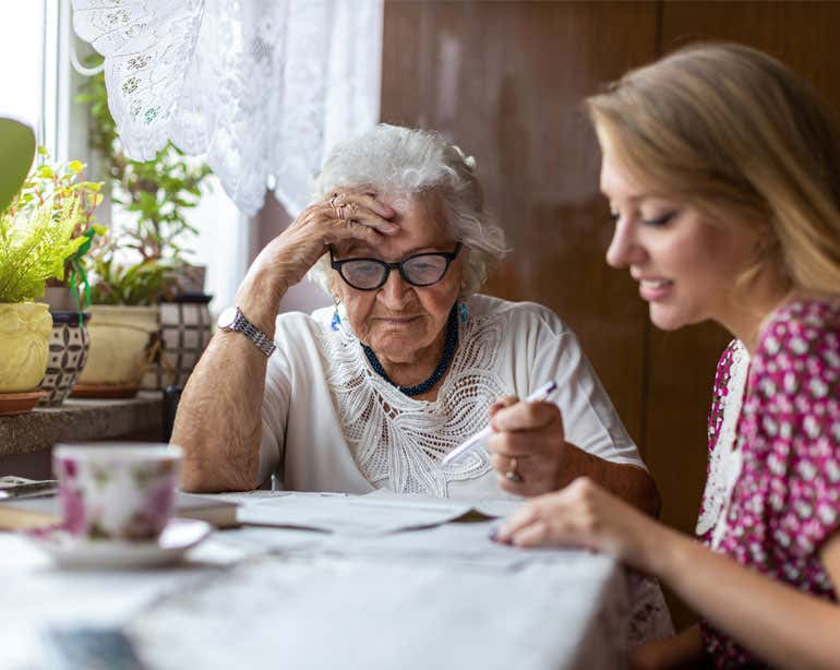 A young female caregiver helps her grandmother with her financial paperwork.