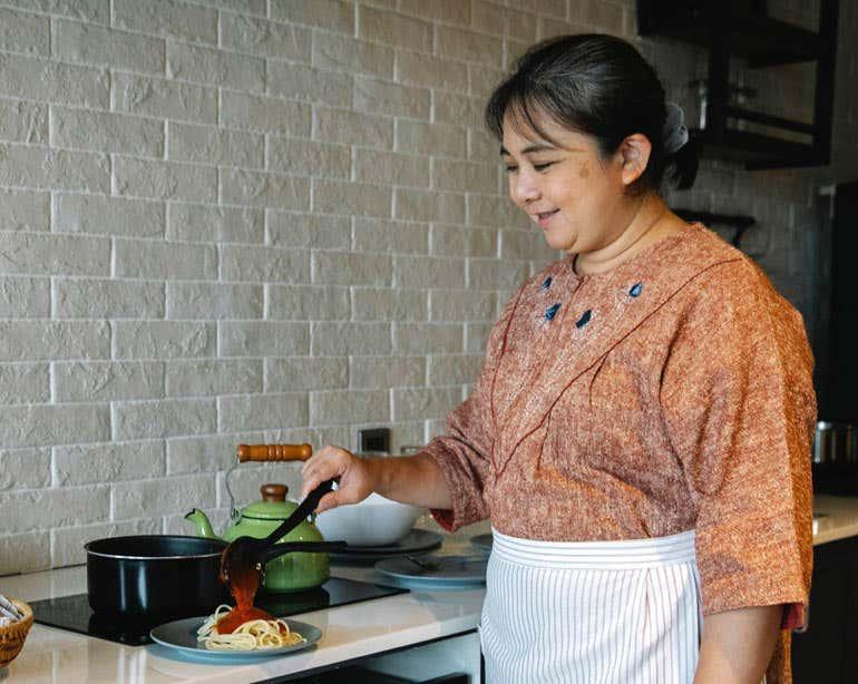 An older Asian senior woman is seen preparing food in her kitchen.