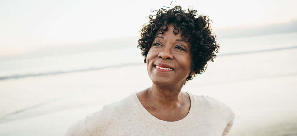 A Black senior woman is gazing off camera while at the beach.