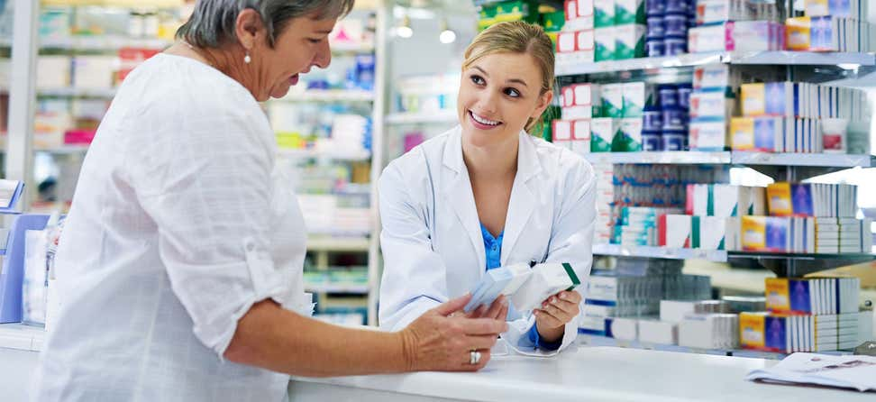 A young pharmacist behind the counter is giving prescription instructions to her senior female client.