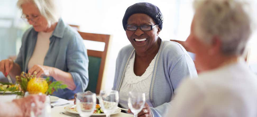 A senior Black lady wearing glasses laughs with her friends during lunchtime at a senior center.