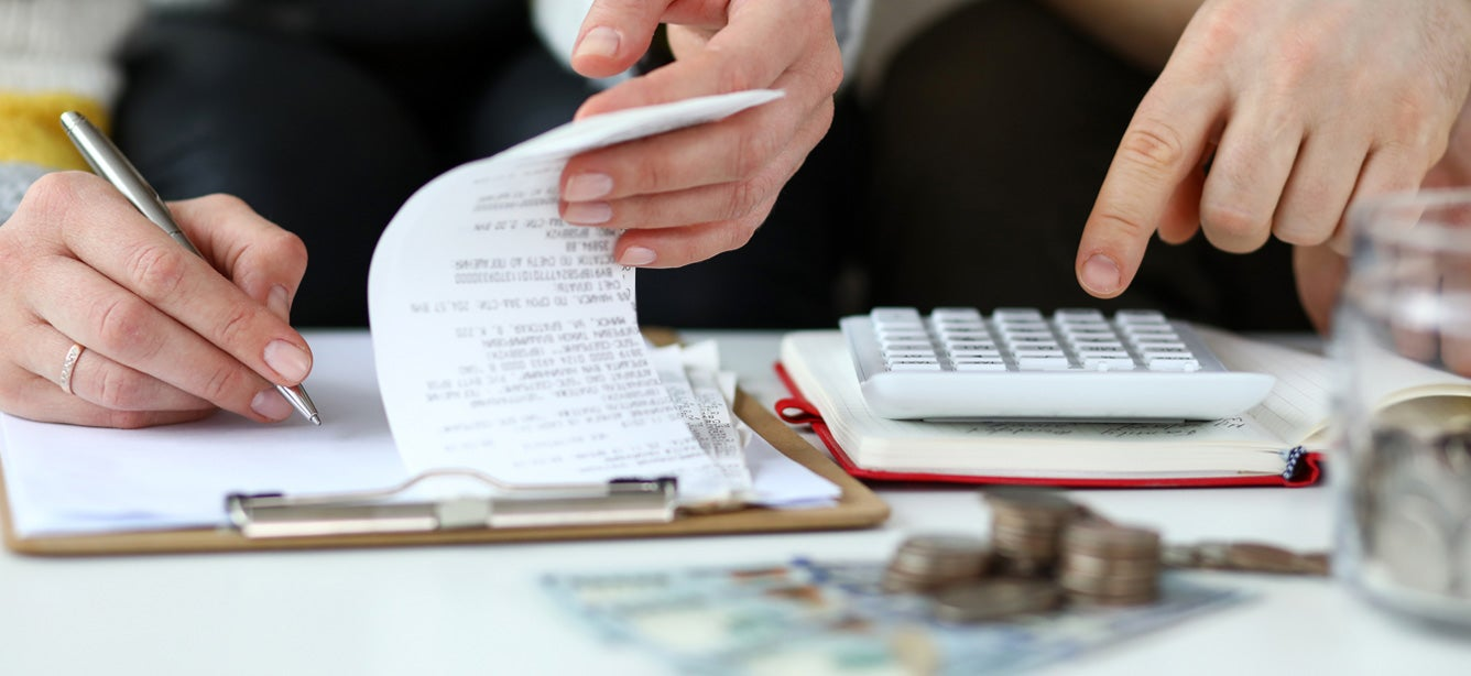 Two people are looking over receipts and other financial paperwork as they work to balance their household budget.