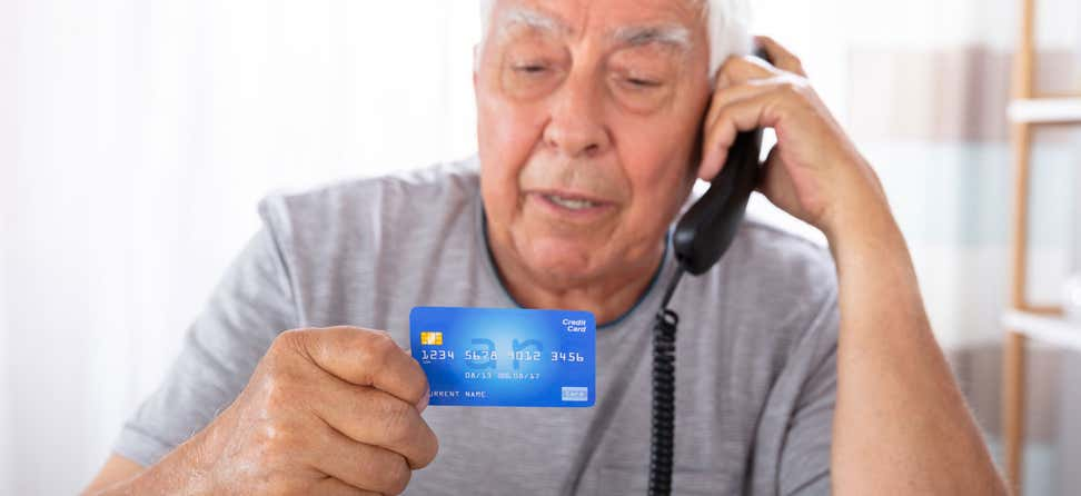 A senior man is on the phone, holding his credit card as if he's going to make a purchase.