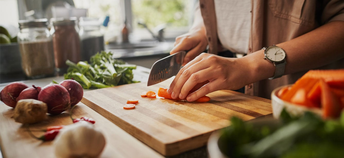 A woman off camera is slicing carrots in her kitchen, among other healthy vegetables.