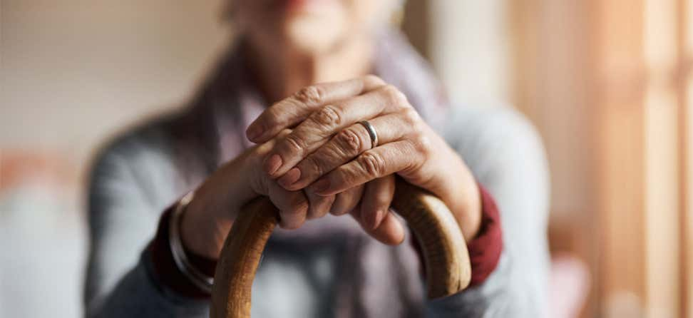A closeup shot of a senior woman holding her cane in a senior center.
