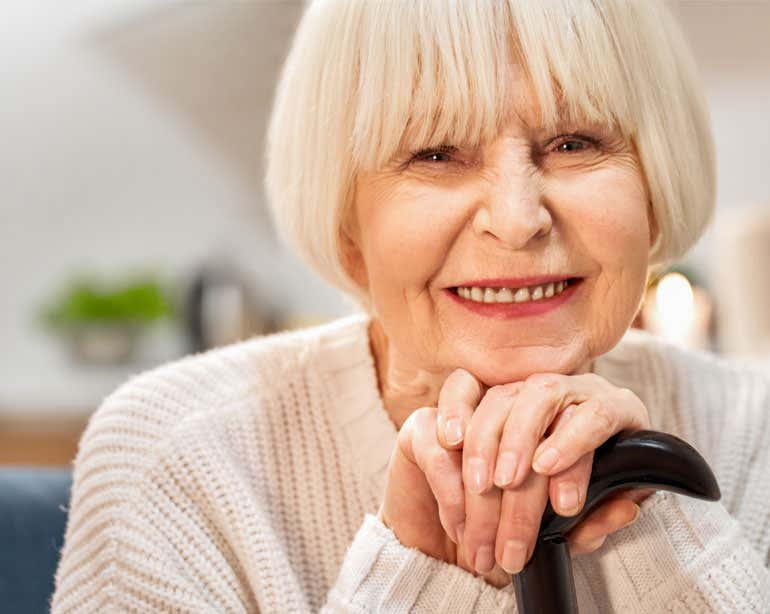 An up close shot of a senior woman smiling at the camera with her hands resting on her cane.
