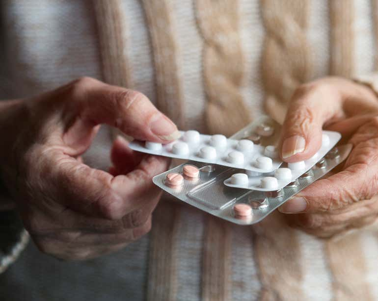 Close up shot of a senior woman holding a few packs of pills in her hands.