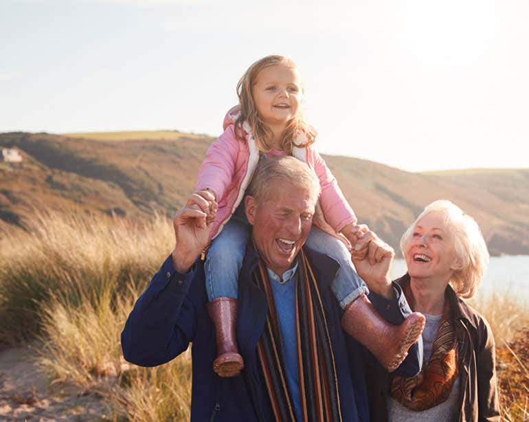 An older adult grandfather has his granddaughter on his shoulders while his wife looks at both of them lovingly.