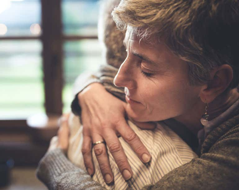 Older woman is seen embracing the senior man that she provides caregiving for.