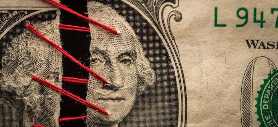 An up-close shot of a dollar bill being stitched together with red thread at George Washington's face.