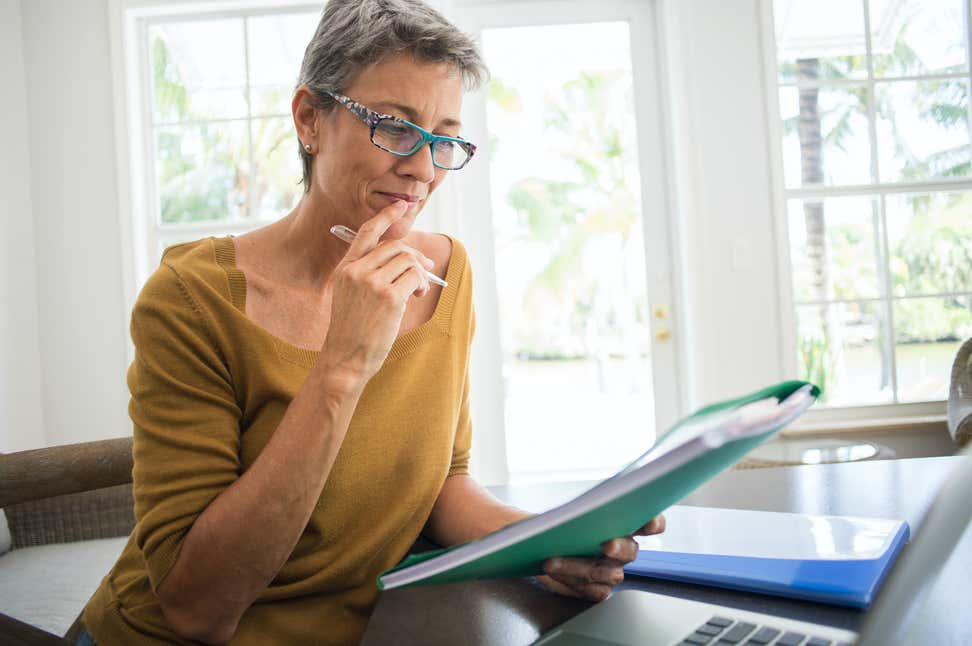 An older woman with glasses looks at paperwork and her laptop with a pen in her hand