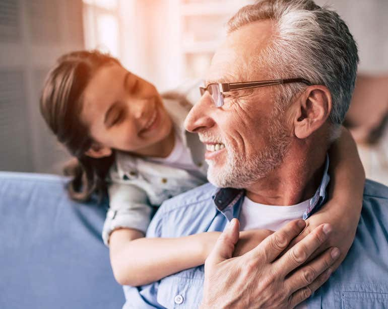 A grandfather with a beard and glasses is being hugged by his granddaughter while he's sitting on the couch. Both are smiling.