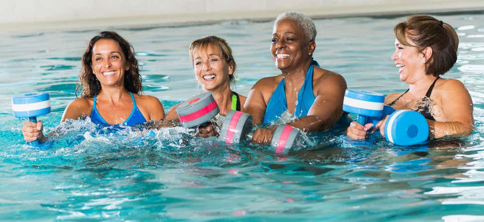 A group of four multi-ethnic senior women are enjoying water aerobics at a senior center.