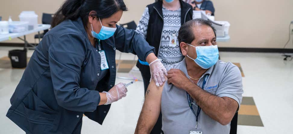 An older adult Hispanic man is receiving his COVID-19 vaccination at the Griffin Senior Center.